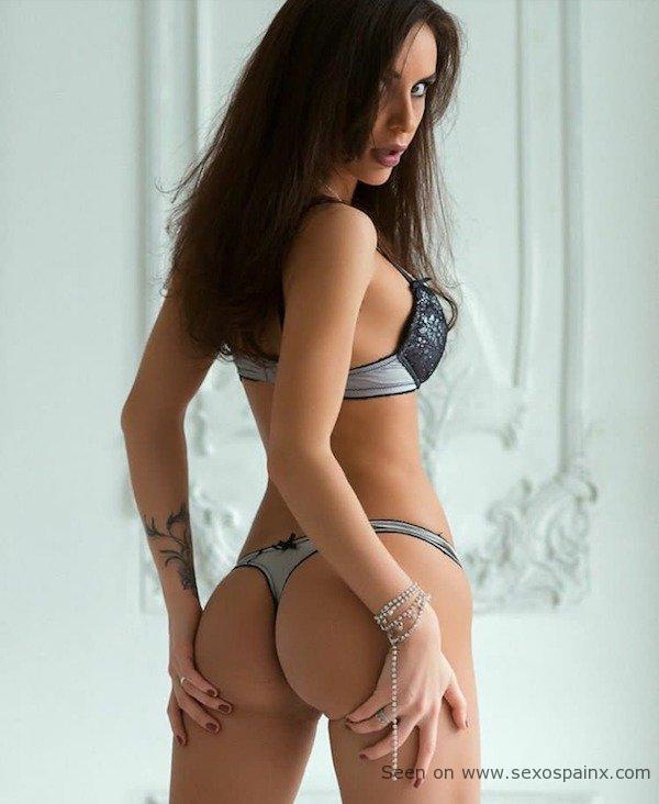 Mujer en lencería resaltando su trasero con un tanga a juego con el sujetador.